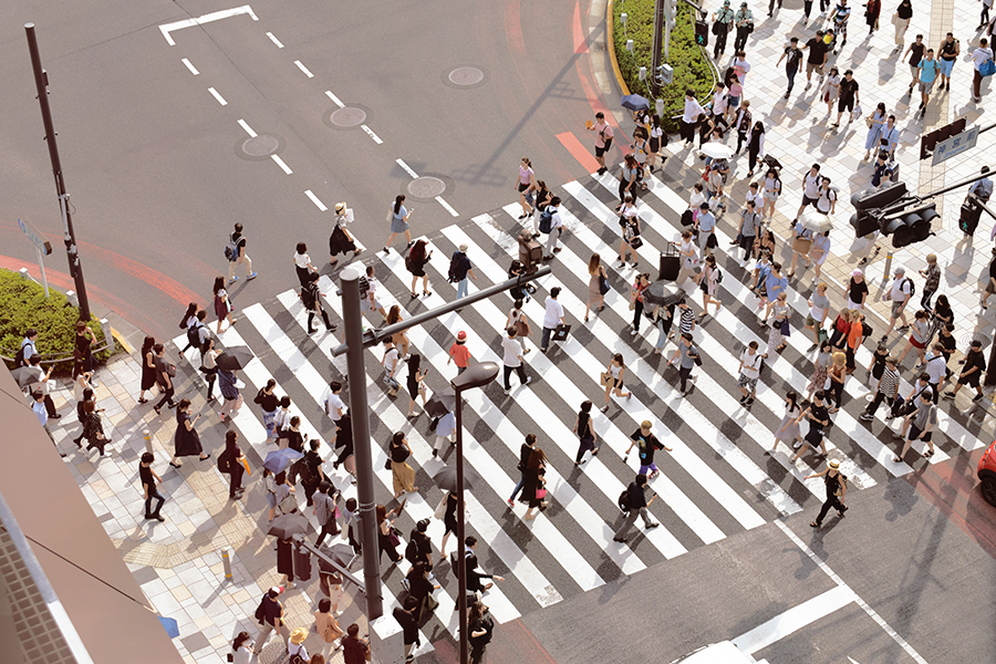 Crowd of people in the city at a crosswalk.